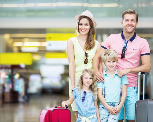 45036230 - happy family with a suitcase at the airport