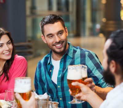 51496547 - leisure, eating, food and drinks, people and holidays concept - smiling friends having dinner and drinking beer at restaurant or pub